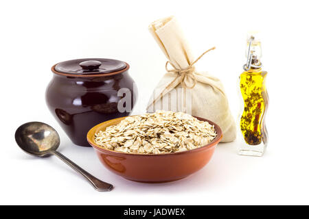 Still life of Oatsmeal cereal in ceramic pial, ceramic pot, old spoon and canvas bag for cereals, oil with spices - Stock Photo