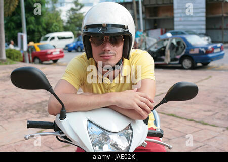 Young man on a scooter wearing sunglasses - Stock Photo