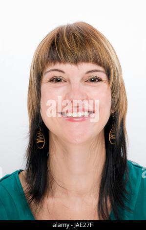 Kopf-und-Schulter-Aufnahme einer jungen Frau mit freudestrahlenden, glücklich lächelnden Blick in die Kamera - Stock Photo