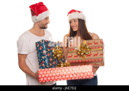 Smiling young couple with large gift-wrapped colourful Christmas gifts standing in their Santa hats looking into - Stock Photo