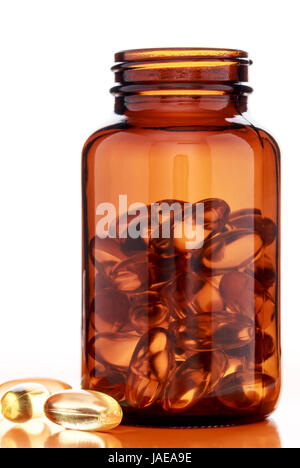 Omega 3 fish oil capsules and glass bottle on a white background - Stock Photo
