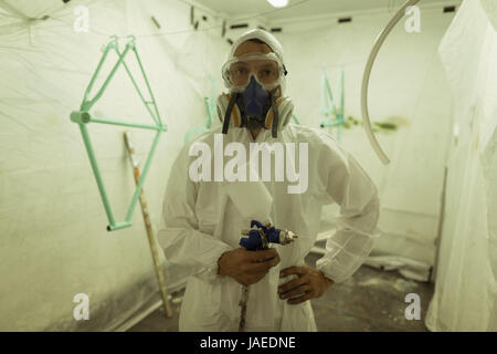 Portrait of painter holding paint spray gun while wearing gas mask at bicycle workshop - Stock Photo