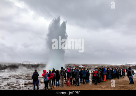 Geysir, Iceland - March 24, 2017: people are waiting for fountain geyser to erupt at Strokkur geyser. Strokkur is - Stock Photo