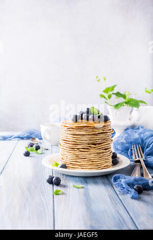 Stack of homemade pancakes with fresh blueberries on a wooden background. Healthy breakfast concept with copy space. - Stock Photo