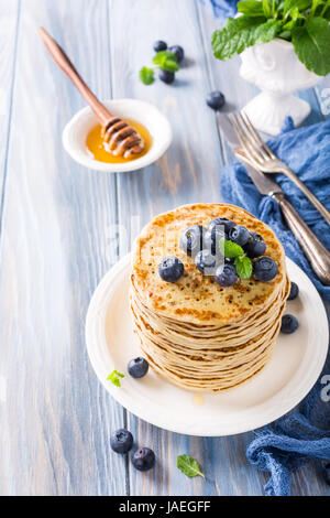 Delicious pancakes with fresh blueberries on a wooden background. Healthy breakfast concept. - Stock Photo
