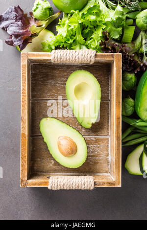 Avocado in wooden tray with assorted green vegetables, salad, bell pepper and Brussels sprouts on light brown stone - Stock Photo