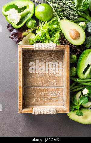 Background with assorted green vegetables, salad, avocado, bell pepper and Brussels sprouts with wooden tray on - Stock Photo