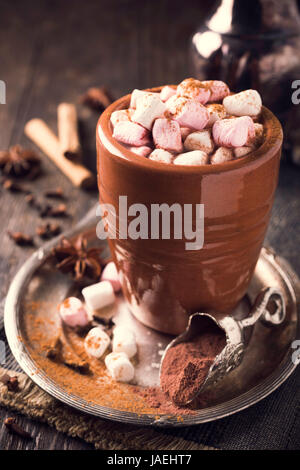 Cup of hot chocolate with mini marshmallows and winter spices on dark wooden background. - Stock Photo
