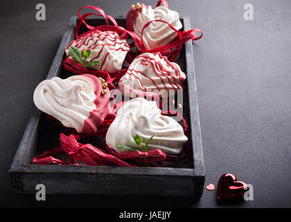 Homemade meringues in heart shape in old wooden box for Valentine's day. - Stock Photo