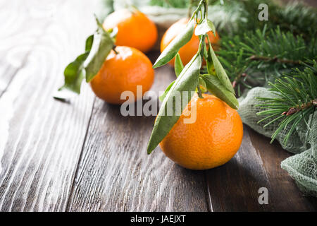Fresh tangerines with leaves and ripe mandarins on wooden table - Stock Photo