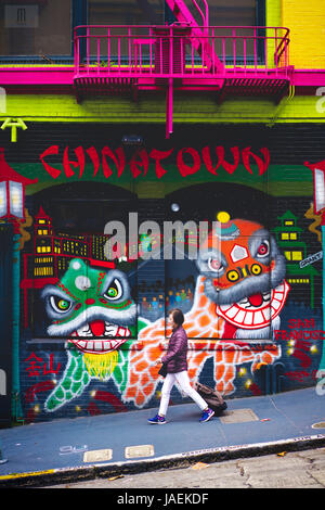 A woman walking down a downward alley past a wall of graffiti portraying Chinese dragon dancing in Chinatown in - Stock Photo