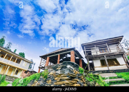 Old and new abandoned wooden houses surrounded by beautiful nature and rocks on top of a hill in a tiny village - Stock Photo