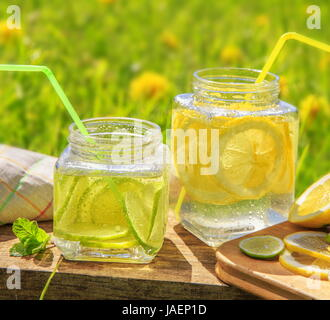 Lemon and lime slices in jars in summer wooden background. - Stock Photo