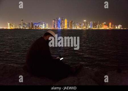 A man sits on the sea wall in Dhow Harbour looking at his mobile phone. In the background is the view across the - Stock Photo