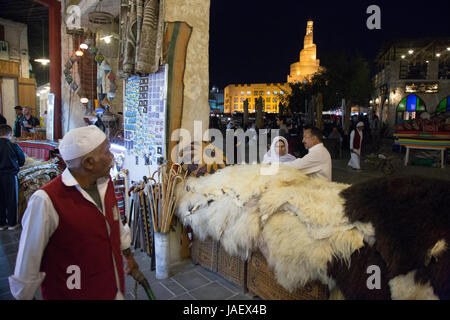 A porter and a couple looking at sheepskins in the regenerated shopping area of Souq Waqif, Doha, Qatar. - Stock Photo