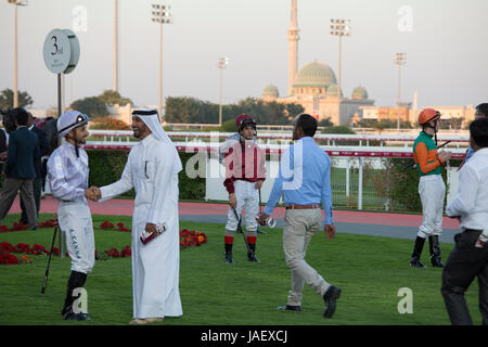 Jockeys and racehorse owners in the paddock before a race at the Racing and Equestrian Club in Doha, Qatar. - Stock Photo