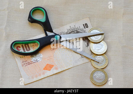 sterling note with open scissors and pound coins on top - Stock Photo
