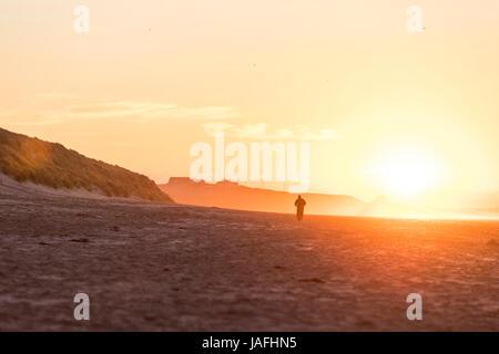 Man exercising on Bamburgh beach, Northumberland, UK. - Stock Photo