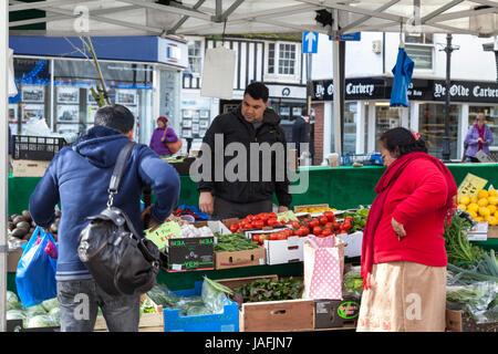 Ashford town centre market stall displaying fresh fruit and vegetables man serving women. Ashford, Kent - Stock Photo
