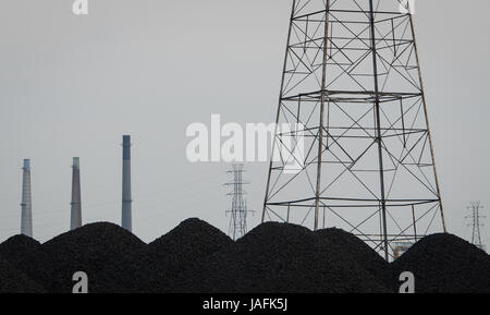 Smokestacks and power lines from the United States Steel Corp. compete for space with piles of coal, slag and petroleum coke on Zug Island where they are stored uncovered along the banks where the Detroit River meets the Rouge River.