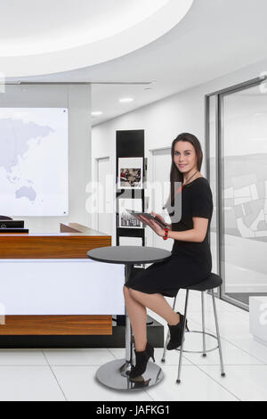 Business, Young woman in smart dress using tablet computer in office setting. - Stock Photo