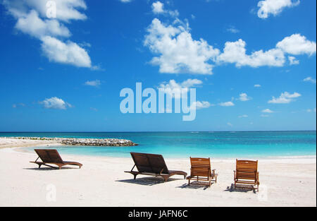lounge chairs at a tropical paradise beach - Stock Photo