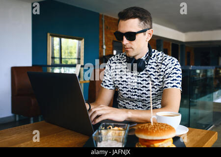 Attractive male worker is using computer in cafeteria