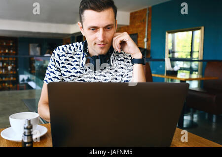 Attractive male worker is using computer in cafeteria - Stock Photo