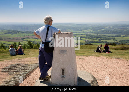 UK, England, Shropshire, The Wrekin, visitor at summit resting on Ordnance Survey trig point - Stock Photo