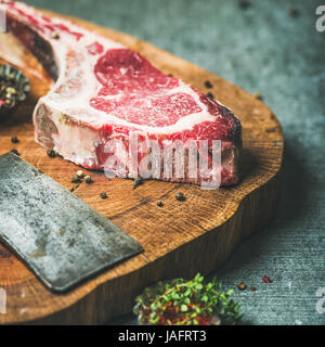 Dry aged raw beef rib eye steak with bone, butcher meat chopping knife and spices on wooden board over grey concrete - Stock Photo