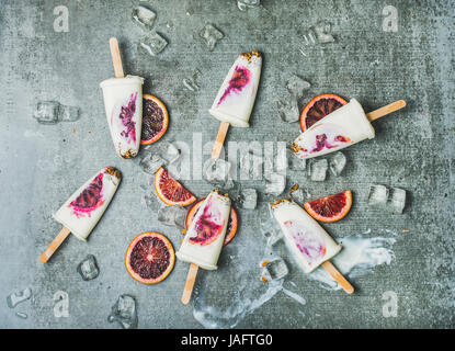 Healthy summer dessert. Blood orange, yogurt and granola popsicles on ice cubes over grey concrete background, top - Stock Photo