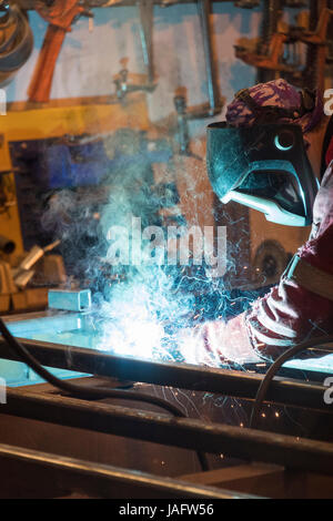 Factory worker welding in a manufacturing plant. - Stock Photo