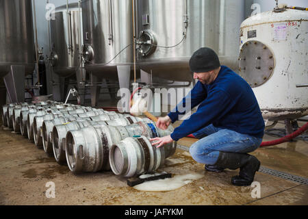 Man kneeling and hammering in a peg into a metal beer keg. Large fermentation tanks. - Stock Photo