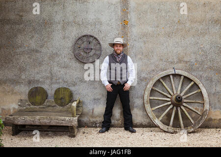 Bearded man wearing Stetson standing with his hands in his pockets outside a barn next to a wooden bench and large - Stock Photo