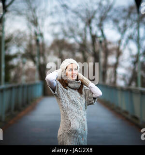 Autumn/winter portrait: young woman dressed in a warm woolen cardigan posing outside in a city park - Stock Photo