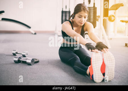 Athletic woman asian warming up and Young female athlete sitting on an exercising and stretching in a gym, healthy - Stock Photo