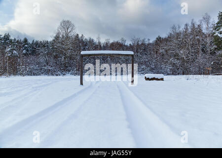 tracks from the wheels of machine on to snow, winter landscape on a glade - Stock Photo