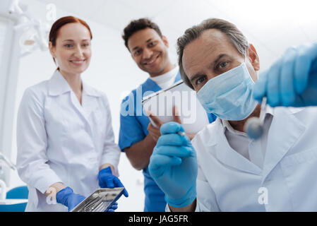 My young coworkers. Positive delighted students in medical uniform looking at their mentor while standing on the - Stock Photo