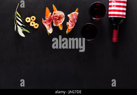Classic Italian appetizer of prosciutto and melon with red wine and taralli on a dark stone naturanom - Stock Photo