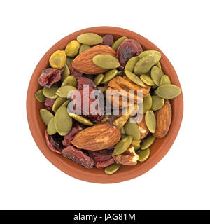 Top view of omega 3 trail mix nuts and fruit in a small clay bowl isolated on a white background. - Stock Photo