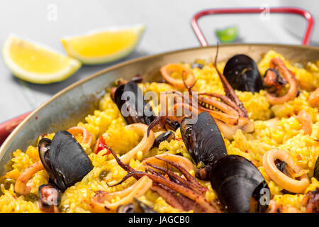 Seafood Paella in Traditional Pan on Rustic Wooden Table Stock Photo