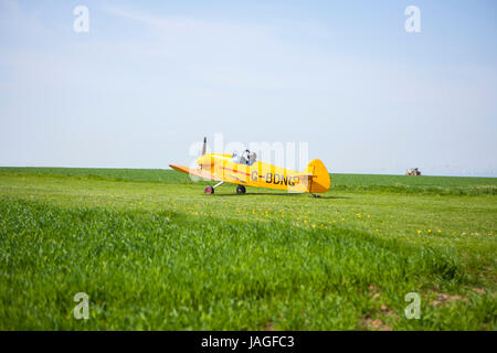very small yellow aircraft taxiing along rural field ready to take off for flight - Stock Photo