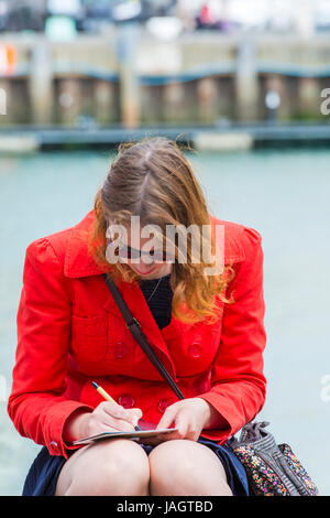 Woman writing postcards sitting on harbourside at Weymouth, Dorset in June - Stock Photo