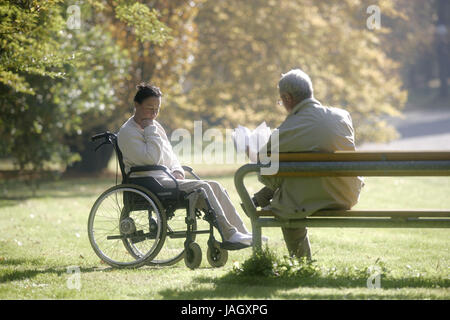 Woman sits in the invalid's wheel chair,man reads on park-bench, - Stock Photo