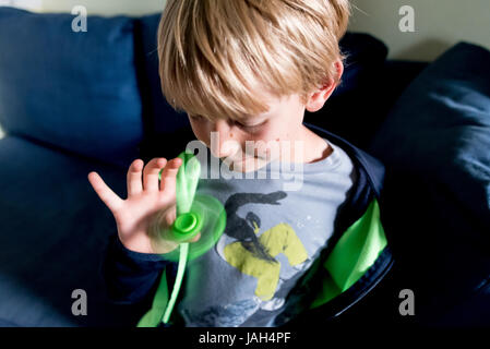 A boy plays with a fidget spinner at home, the controversial stress relief toy found to help some antsy or autistic - Stock Photo