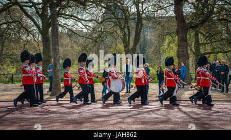 Guardsmen of the Queen's Guard, Royal Guards in red uniform on the way to Buckingham Palace, Changing of the Guard, - Stock Photo