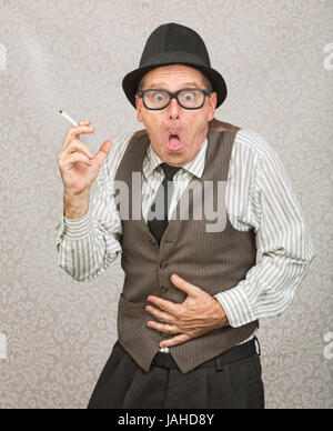 Single man holding cigarette with upset stomach - Stock Photo