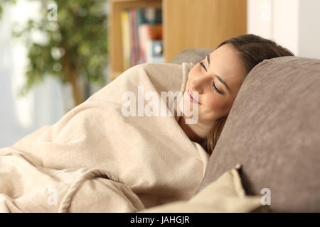 Relaxed girl sleeping covered with a warmly blanket sitting on a comfortable couch in the living room at home - Stock Photo