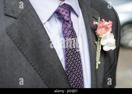Pink rose boutonniere flower groom wedding coat with tie and shirt - Stock Photo