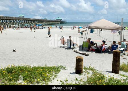 Tourists enjoying Folly Beach in Charleston, South Carolina, USA. - Stock Photo